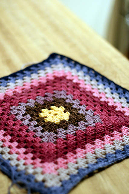 a crocheted granny square blanket in rich jewel tones