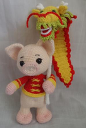 Amigurumi pig holding a dragon