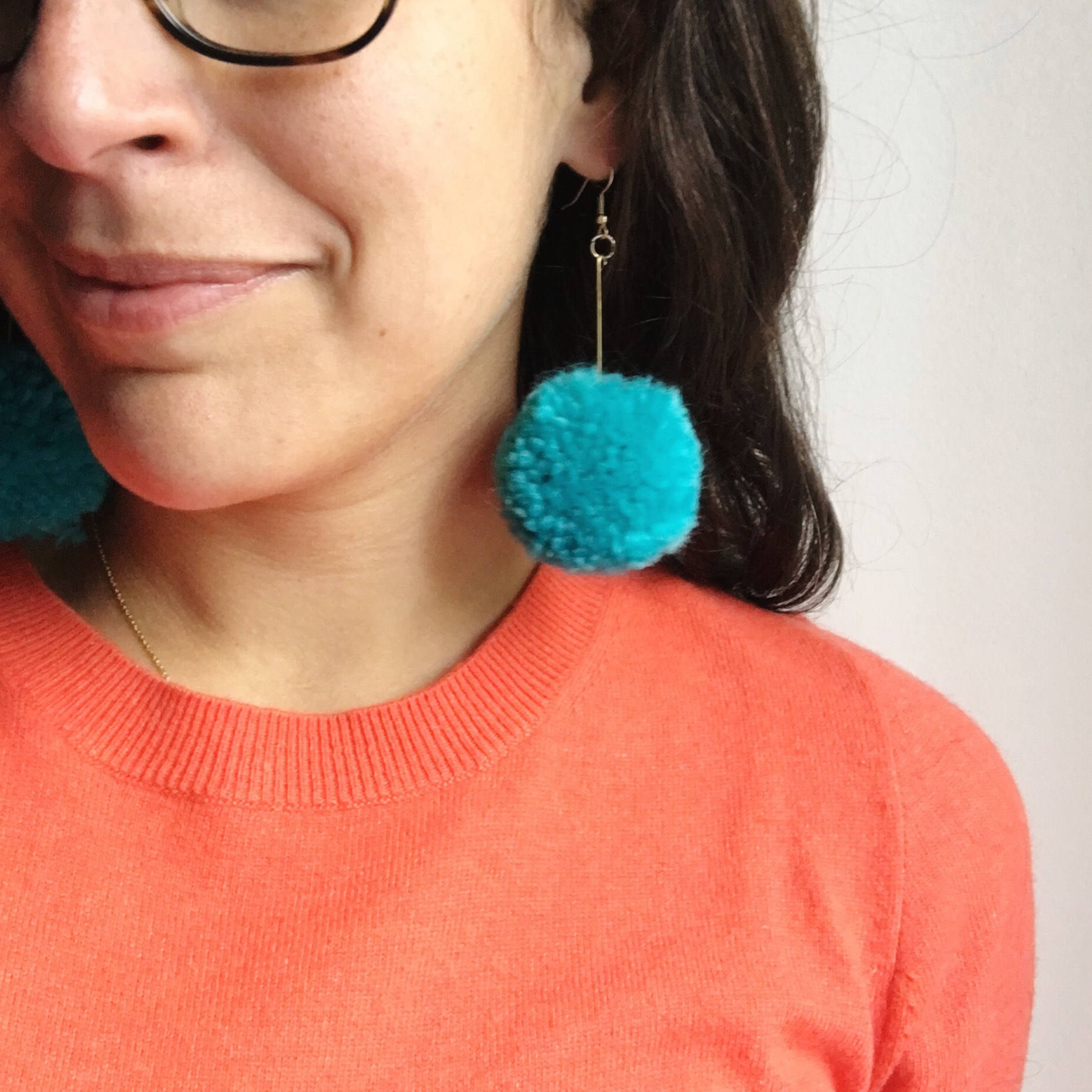 woman wearing an orange shirt and modeling bright teal pompom earrings
