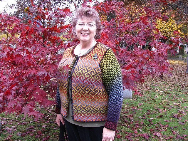 Raveler shrouderknits smiles, looking at the camera, wearing her Turkish Delight cardigan